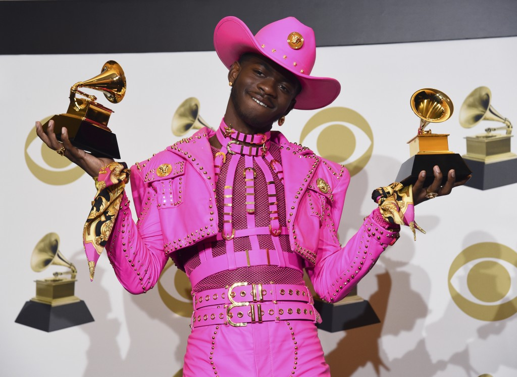 """Lil Nas X poses in the press room with the awards for best music video and best pop duo/group performance for """"Old Town Road,"""" at the 62nd annual Gram..."""