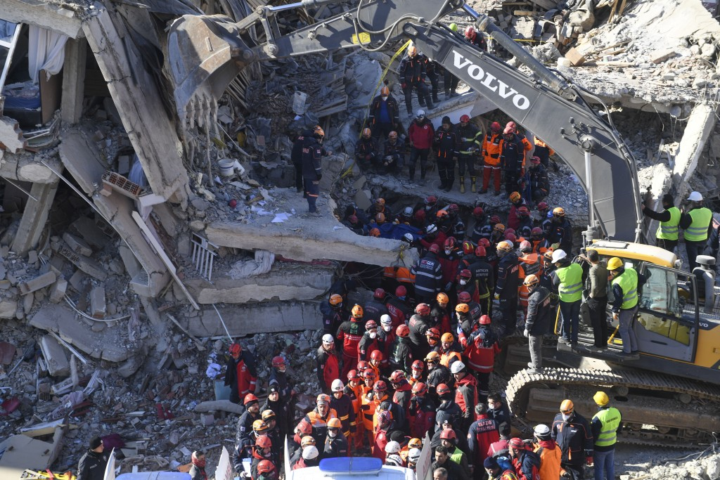 Rescue workers continue to look for people trapped under debris following a strong earthquake that destroyed several buildings on Friday, in Elazig, e...