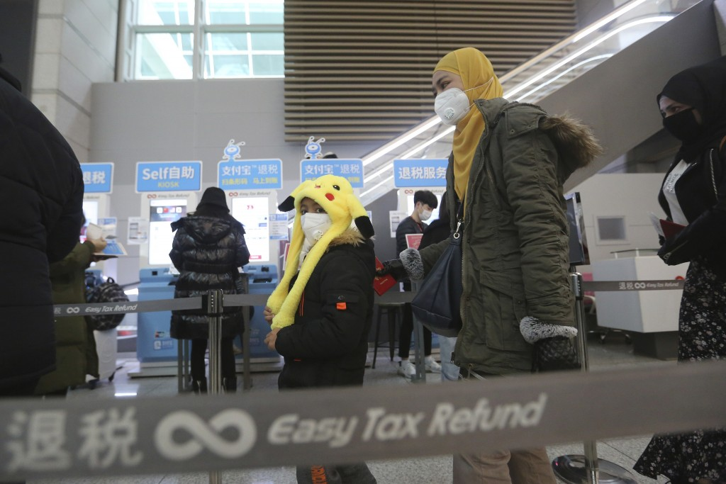 Passengers wear masks in a departure lobby at Incheon International Airport in Incheon, South Korea, Monday, Jan. 27, 2020. China on Monday expanded s...