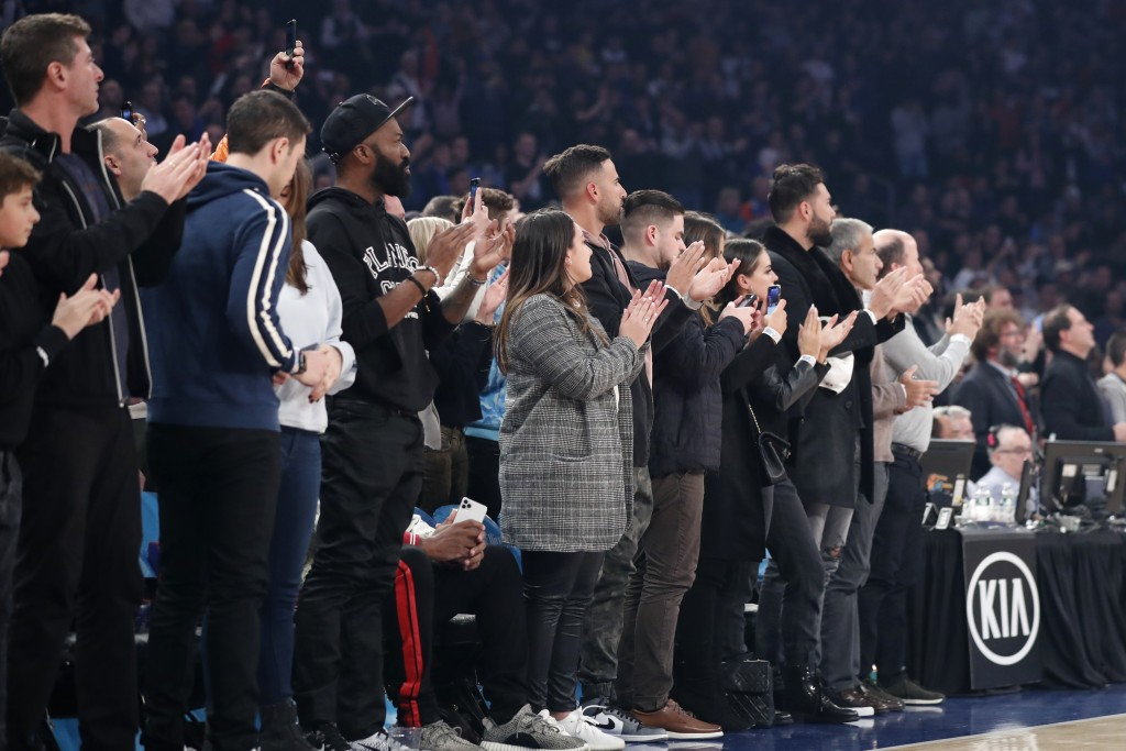 Fans applaud as players hold onto the ball as the 24 second clock runs out in a tribute to retired Los Angeles Lakers star Kobe Bryant who died in a h...