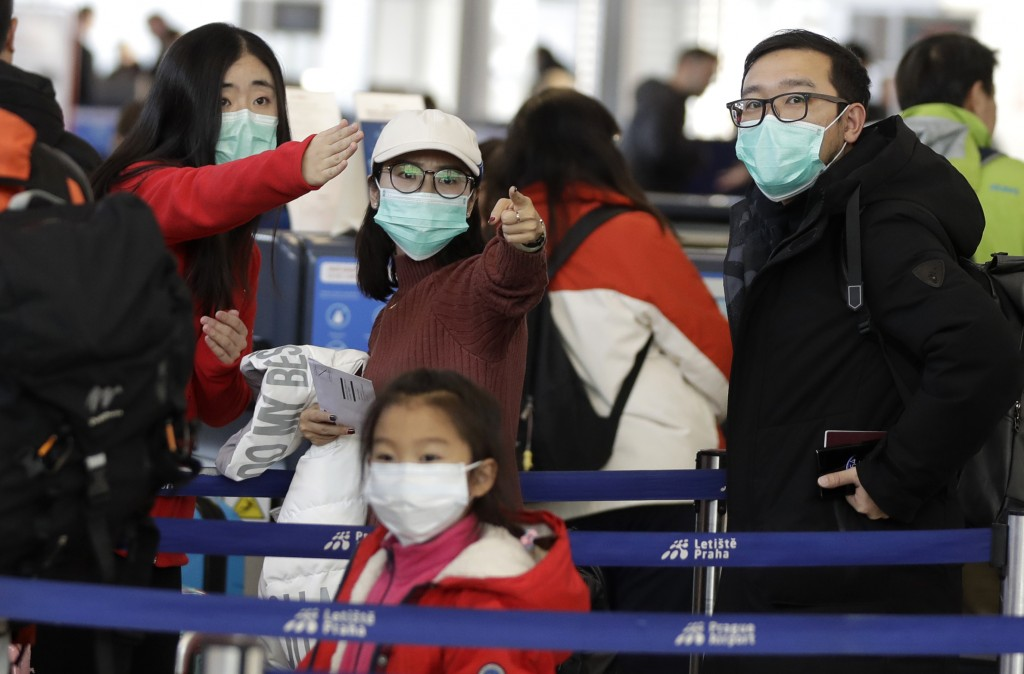 Passengers wearing masks wait in a line to check-in to a flight to Shanghai at the Vaclav Havel International Airport in Prague, Czech Republic, Monda...