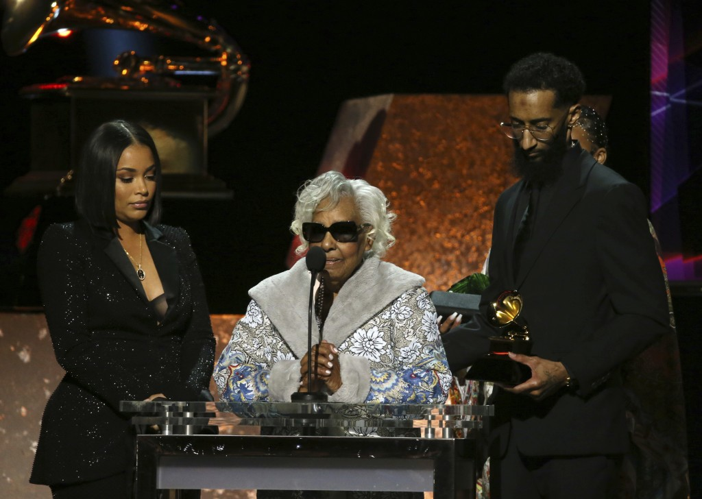 """Lauren London, from left, Margaret Boutte, and Samiel Asghedom accept the award for best rap performance for """"Racks in the Middle"""" on behalf of Nipsey..."""