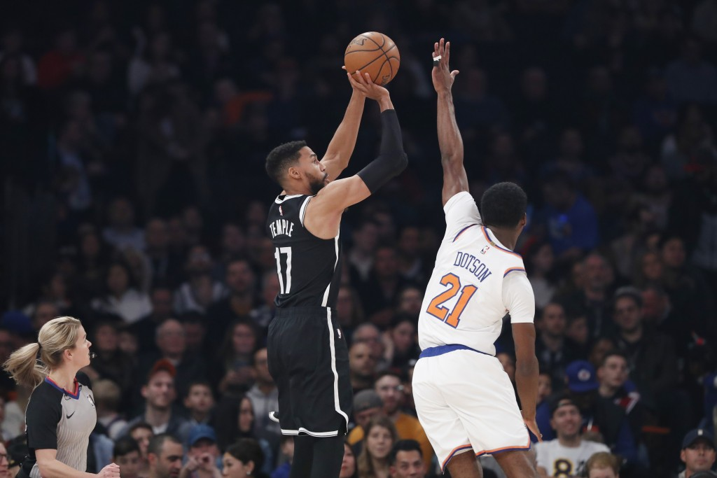 Brooklyn Nets guard Garrett Temple (17) shoots for three points as New York Knicks guard Damyean Dotson (21) defends during the first half of an NBA b...
