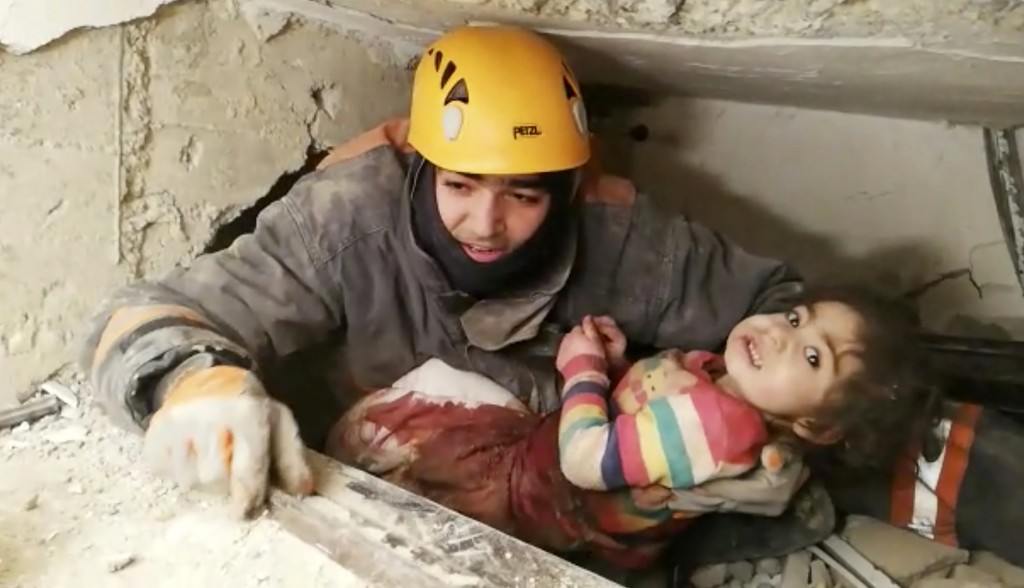 In this image taken from video made available by Ankara Municipality Fire Department shows a rescuer pulling out a girl from the rubble of a collapsed...