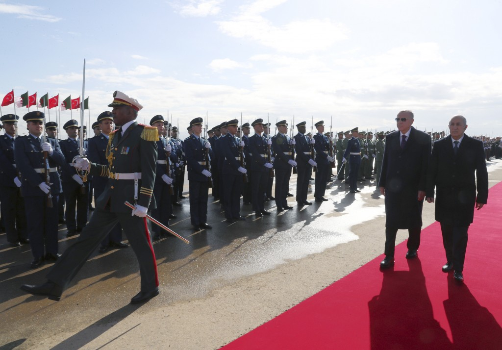 Algeria's President Abdelmadjid Tebboune, right, and Turkey's President Recep Tayyip Erdogan review a military honour guard during a welcoming ceremon...