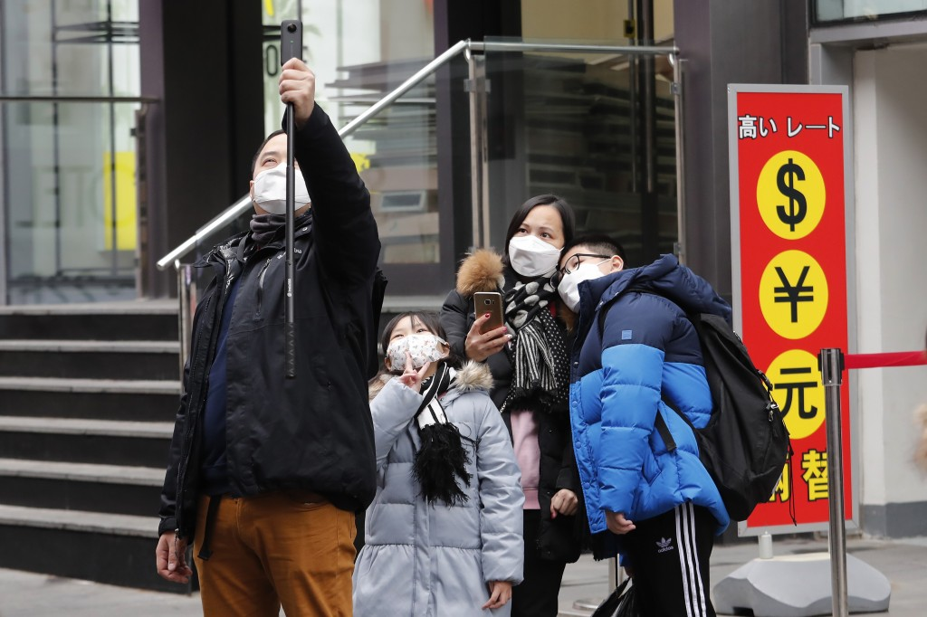 People wearing masks take photos at a shopping district in Seoul, South Korea, Tuesday, Jan. 28, 2020. Panic and pollution drive the market for protec...