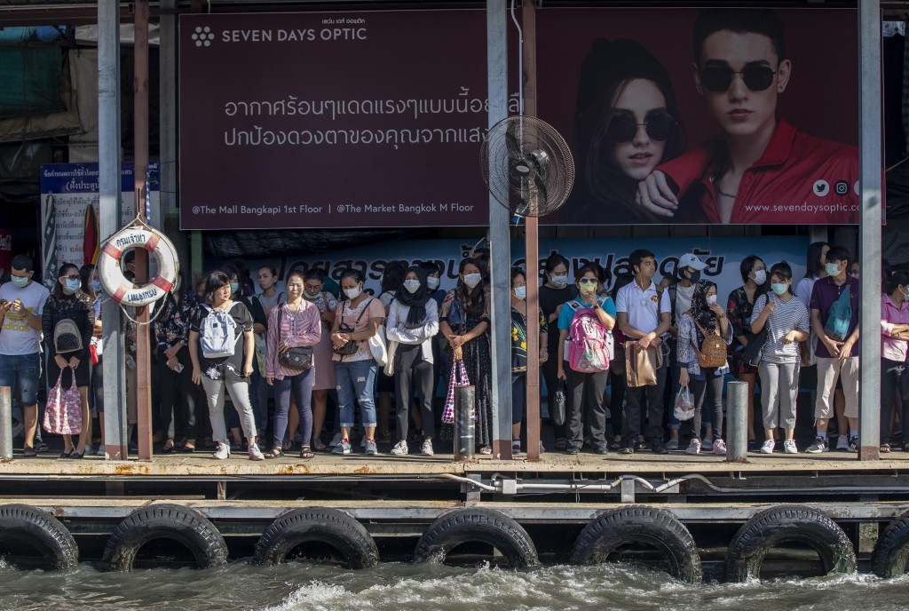Boat passengers on a jetty wear face masks in Bangkok, Thailand, Tuesday, Jan. 28, 2020, to protect themselves from new virus infection. Panic and pol...