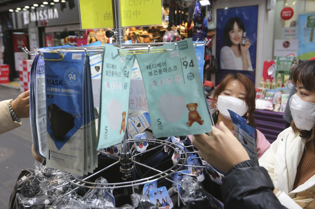 People buy face masks at a shop in Seoul, South Korea, Tuesday, Jan. 28, 2020. Panic and pollution drive the market for protective face masks, so busi...