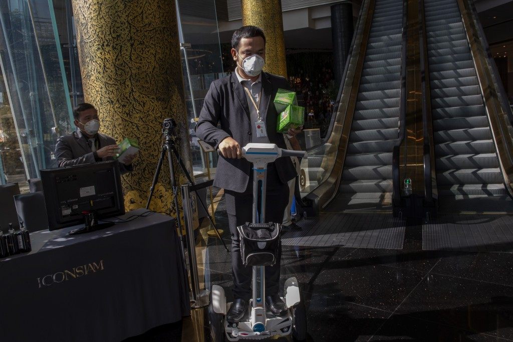 A man on an air-wheel carry protective face masks to be distributed for visitors at a luxury mall in Bangkok, Thailand, Tuesday, Jan. 28, 2020. Panic ...