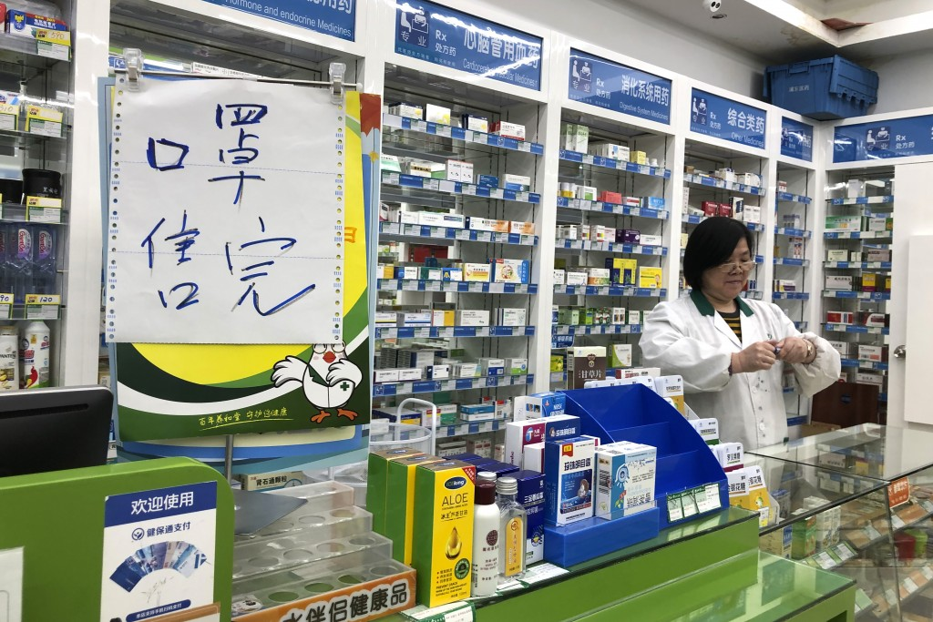 """FILE - In this Tuesday, Jan. 21, 2020, file photo, pharmacist Liu Zhuzhen stands near a sign reading """"face masks are sold out"""" at her pharmacy in Shan..."""
