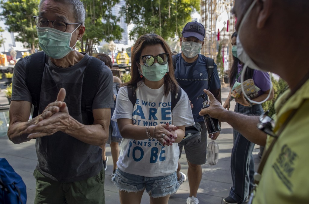 A doorman distributes hand sanitizing liquid for visitors at a luxury mall in Bangkok, Thailand, Tuesday, Jan. 28, 2020. Panic and pollution drive the...