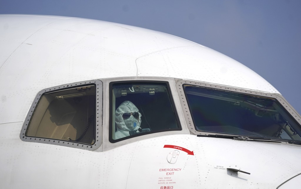 In this Tuesday, Jan. 28, 2020, file photo released by China's Xinhua News Agency, a pilot wearing a protective suit parks a cargo plane at Wuhan Tian...