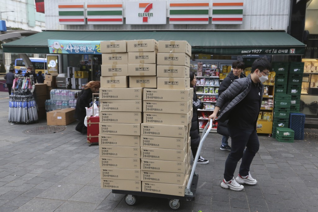 A worker carries boxes containing face masks to a pharmacy at a shopping district in Seoul, South Korea, Tuesday, Jan. 28, 2020. Panic and pollution d...
