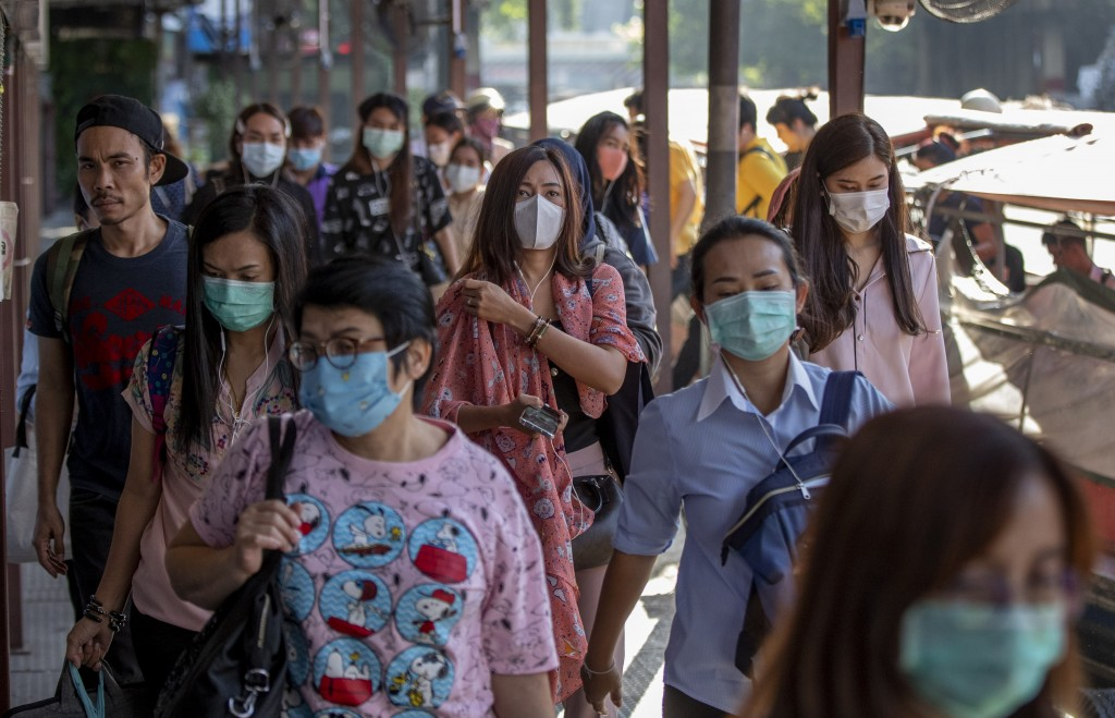 Boat passengers on a jetty wear face masks in Bangkok, Thailand, Tuesday, Jan. 28, 2020 to protect themselves from new virus infection. Panic and poll...