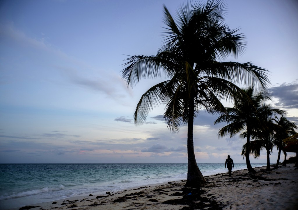 FILE - This Aug. 31, 2019 file photo shows a woman walking along a beach before the arrival of Hurricane Dorian in Freeport, Grand Bahama, Bahamas. Ai...
