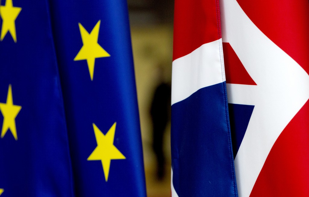 A security guard stands between the Union flag and the EU flag inside the atrium at the Europa building in Brussels, Tuesday, Jan. 28, 2020. The U.K. ...