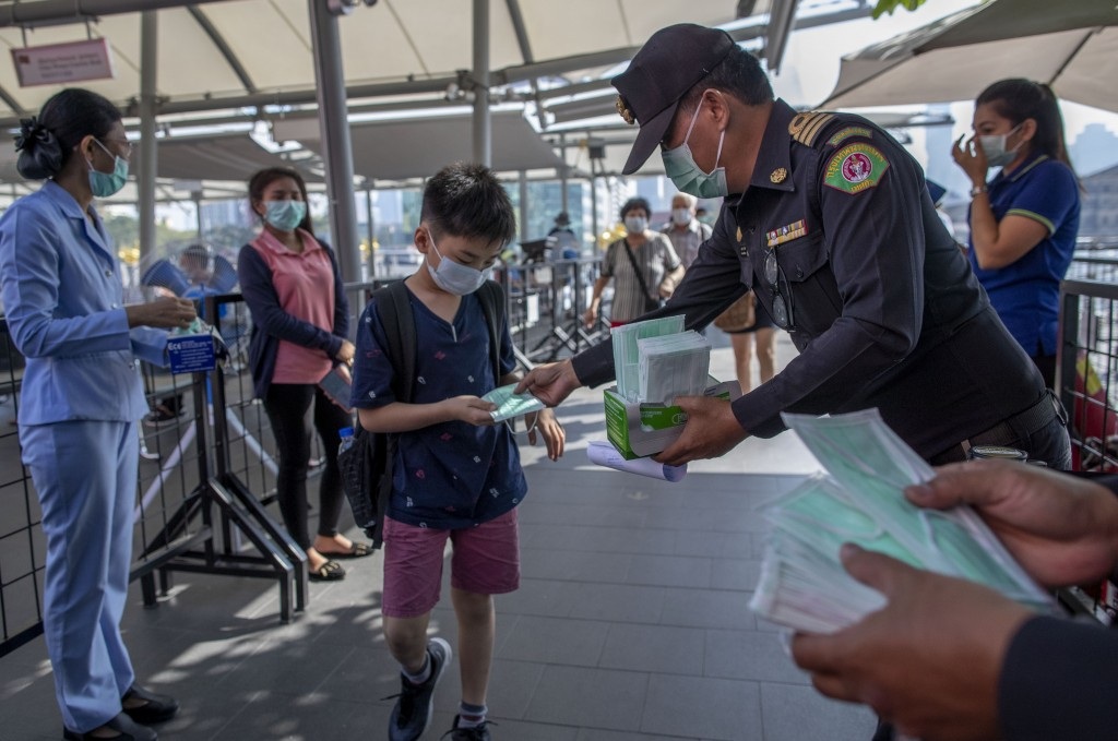 Health officials distribute protective face masks for visitors at a luxury mall in Bangkok, Thailand, Tuesday, Jan. 28, 2020. Panic and pollution driv...