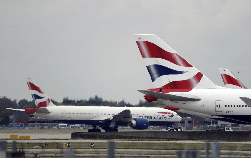 FILE - In this Monday, Sept. 9, 2019 file photo, a British Airways plane, at left, is towed past other planes sitting parked at Heathrow Airport in Lo...