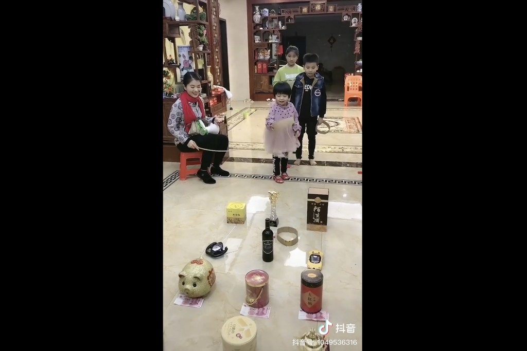 In this Monday, Jan. 27, 2020, image from video posted on Douyin, a popular Chinese social media platform, a mother, left, and children play a traditi...