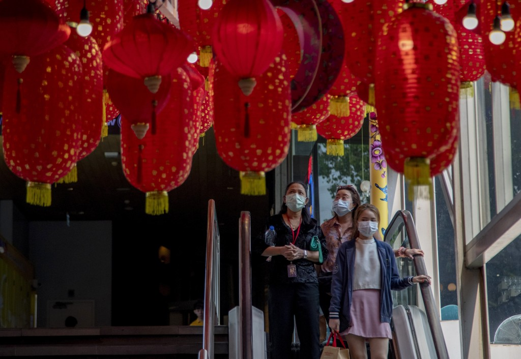 Shoppers wearing face masks use an escalator beneath Chinese New Year decorations in a shopping mall Bangkok, Thailand, Wednesday, Jan. 29, 2020. Tour...