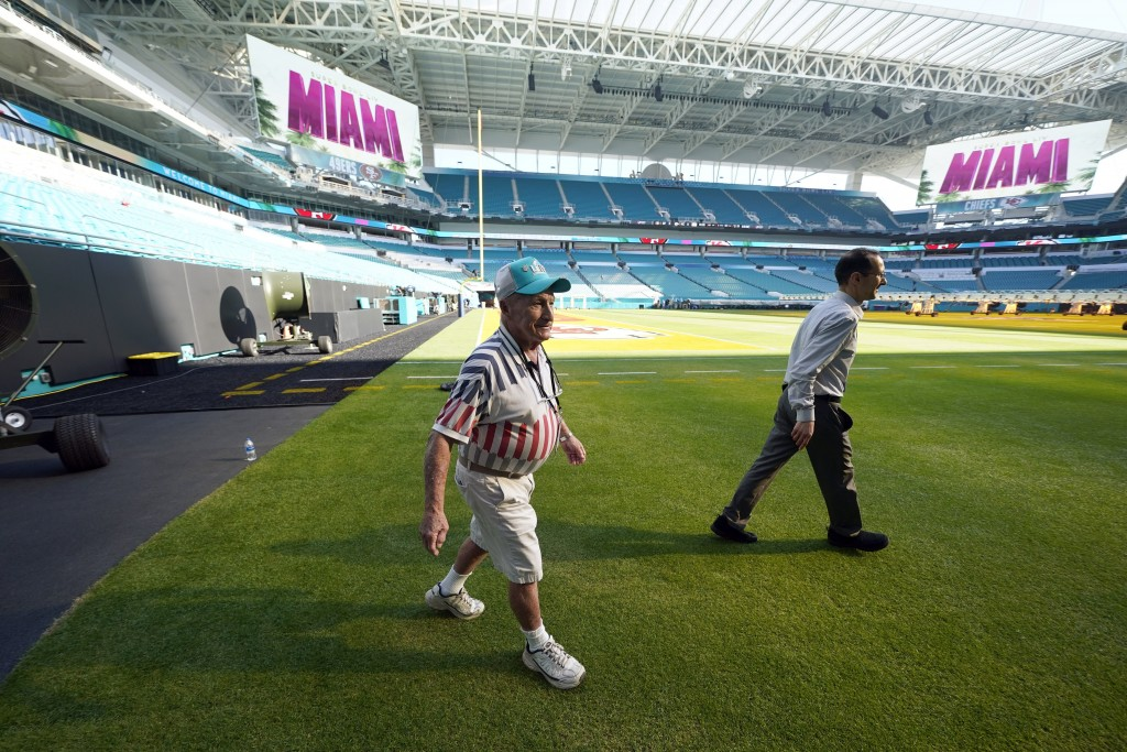 Super Bowl Groundskeeper George Toma, left, walks along the sideline of Hard Rock Stadium Tuesday, Jan. 28, 2020, in Miami Gardens, Fla., in preparati...