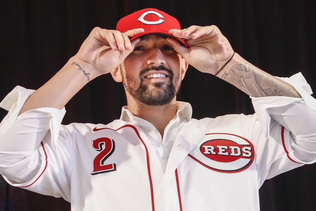 Cincinnati Reds' Nick Castellanos puts on his cap during a news conference, Tuesday, Jan. 28, 2020, in Cincinnati. Castellanos signed a $64 million, f...