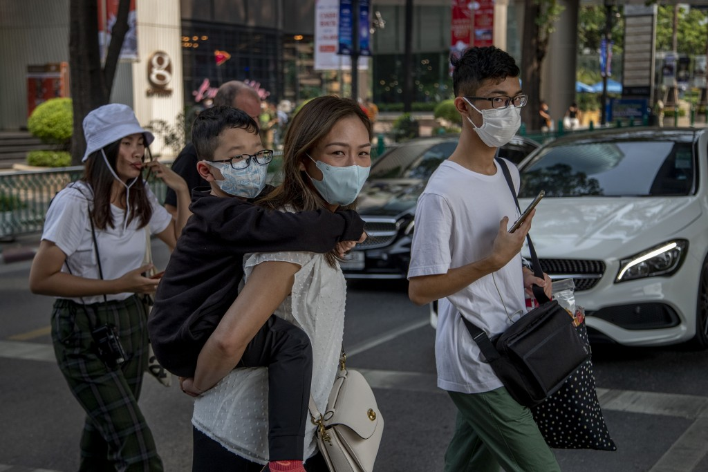 Chinese family wearing face masks walk in a pedestrian crossing in Bangkok, Thailand, Wednesday, Jan. 29, 2020. Tourism Council of Thailand said Tuesd...