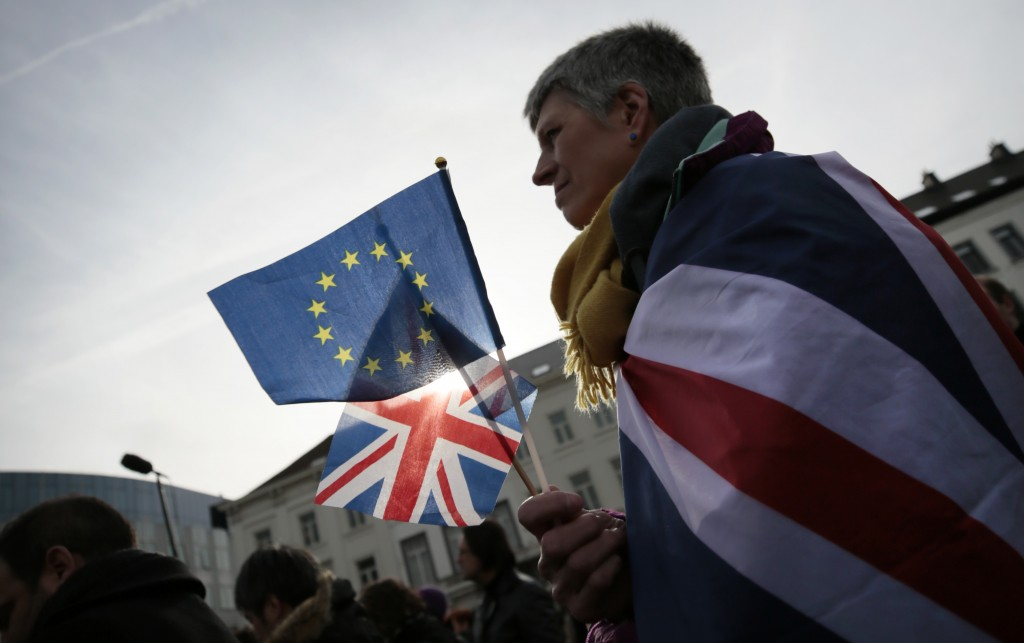 Pro-EU supporter Izzy Knowles, from Birmingham, England, wears a flag with a merger of the Union and EU flags during a ceremony to celebrate British a...