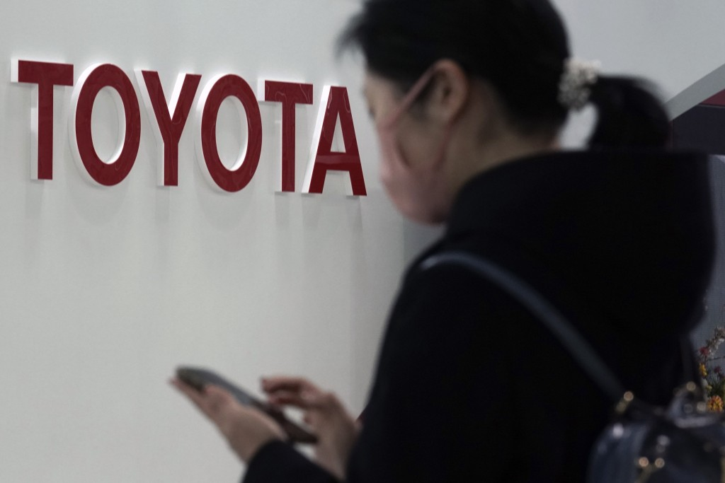 A visitor stands by the logo of Toyota at its showroom Thursday, Jan. 30, 2020, in Tokyo. German automaker Volkswagen has kept its lead as the world's...