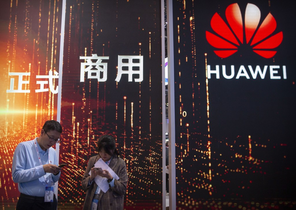 In this Oct. 31, 2019 photo, attendees use their smartphones near a Huawei booth at the PT Expo technology conference in Beijing. Chinese tech giant H...
