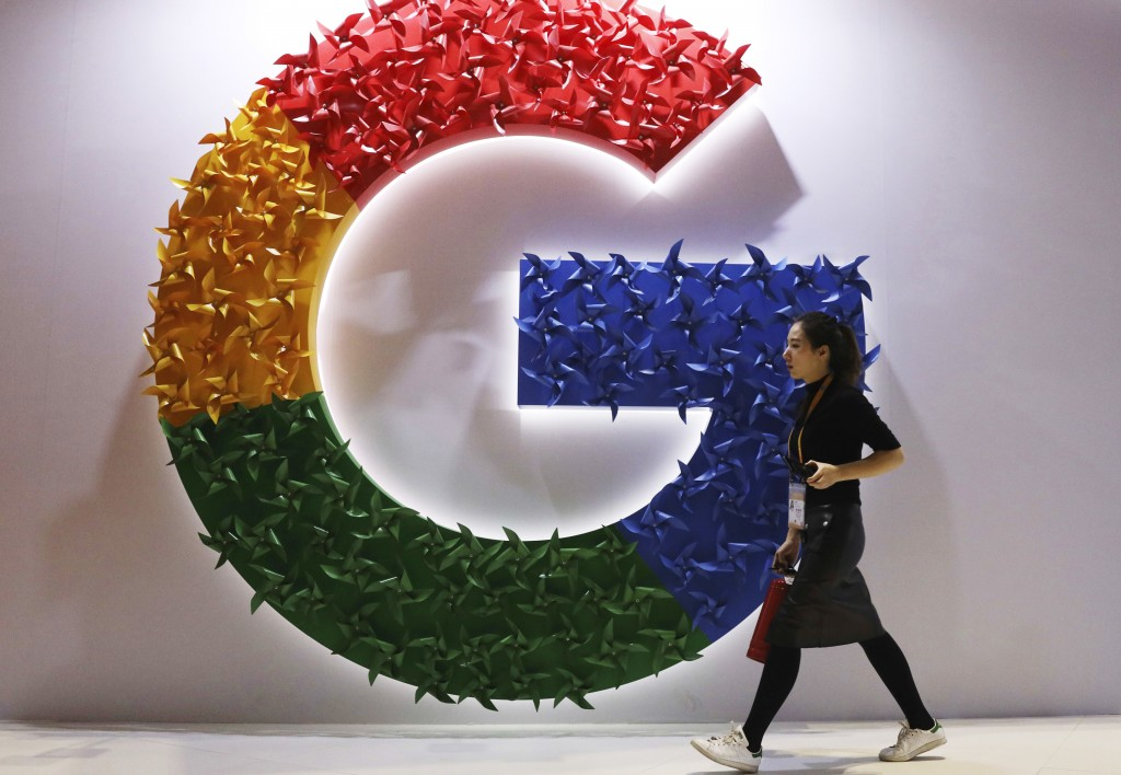 FILE - In this Monday, Nov. 5, 2018, file photo, a woman walks past the logo for Google at the China International Import Expo in Shanghai. Chinese te...