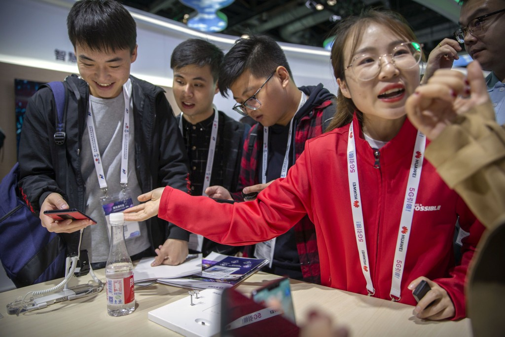 In this Oct. 31, 2019 photo, an exhibitor talks about Huawei smartphones at a Huawei booth at the PT Expo technology conference in Beijing. Chinese te...