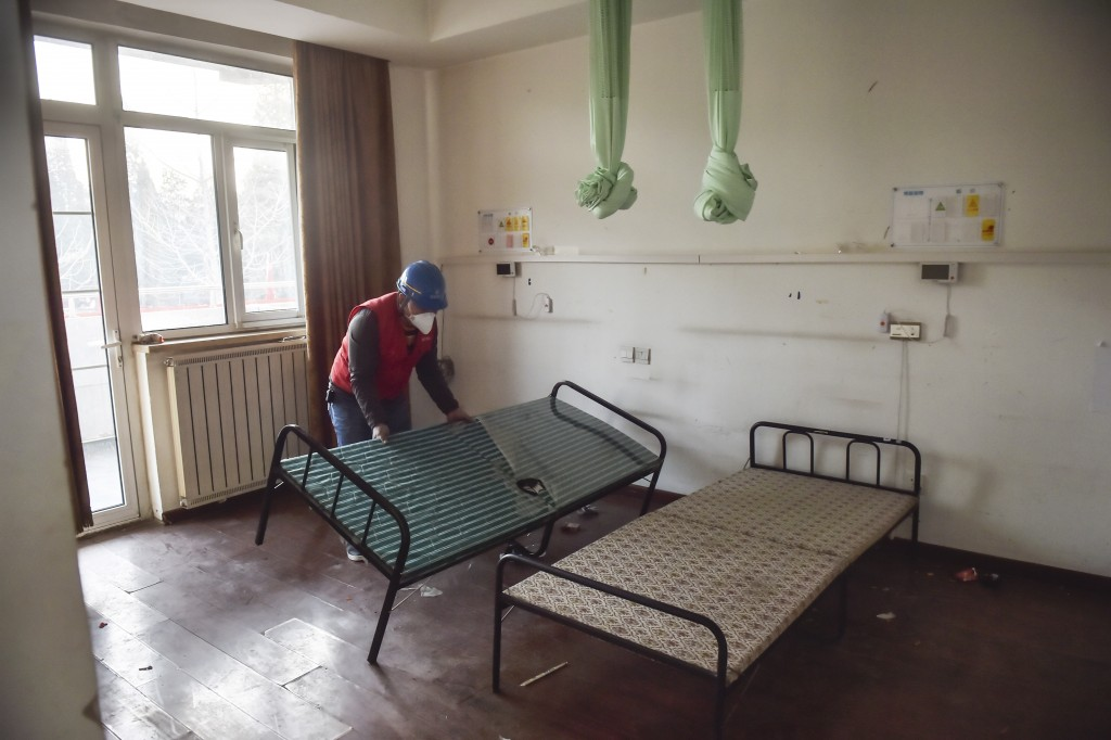 In this photo released by China's Xinhua News Agency, a worker moves a bed during renovations at the Xiaotangshan Hospital in Beijing, Thursday, Jan. ...