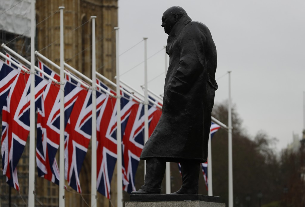 Union flags hang outside Parliament near the statue of Winston Churchill in London, Thursday, Jan. 30, 2020. Although Britain formally leaves the Euro...