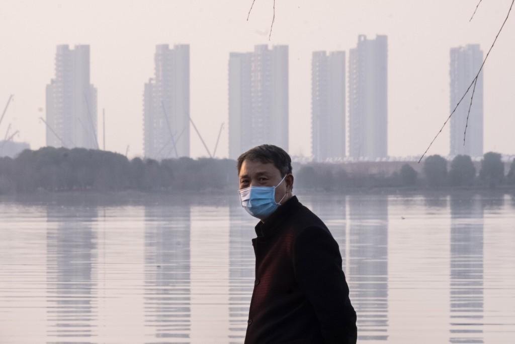 A man wears a face mask as he stands along the waterfront in Wuhan in central China's Hubei Province, Thursday, Jan. 30, 2020. China counted 170 death...