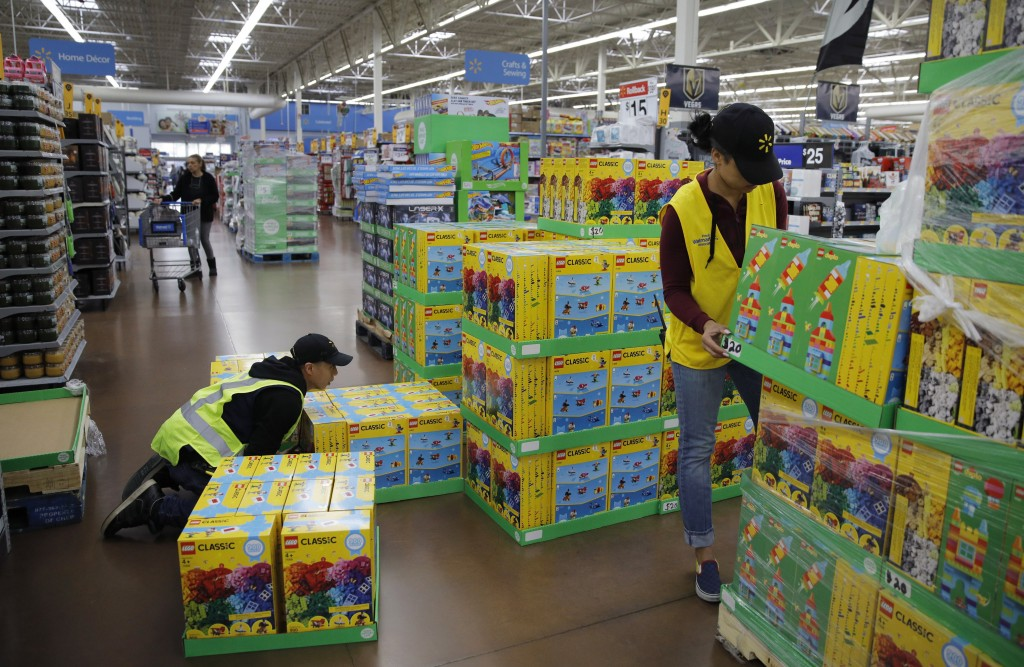 FILE - In this Nov. 27, 2019, file photo Jayln Martin, right, and Dan Villegas stock items in preparation for a holiday sale at a Walmart Supercenter ...