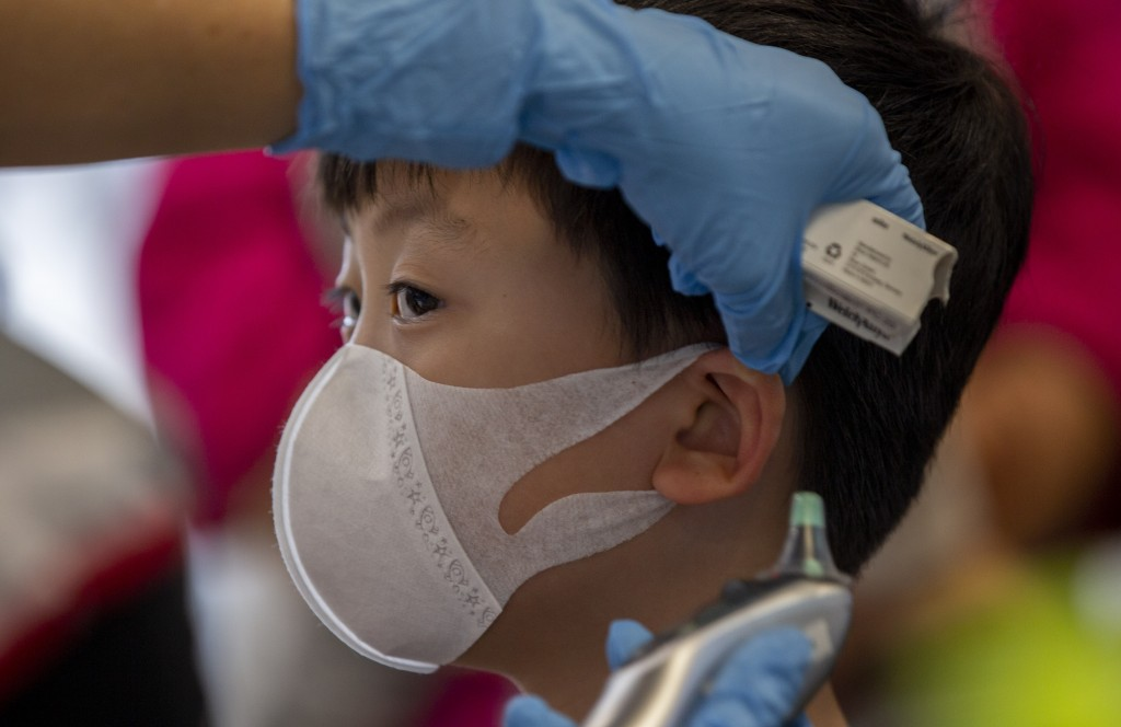A health worker checks the temperature of tourist from Wuhan, China, as he waits for a charter flight back to Wuhan at the Suvarnabhumi airport, Bangk...