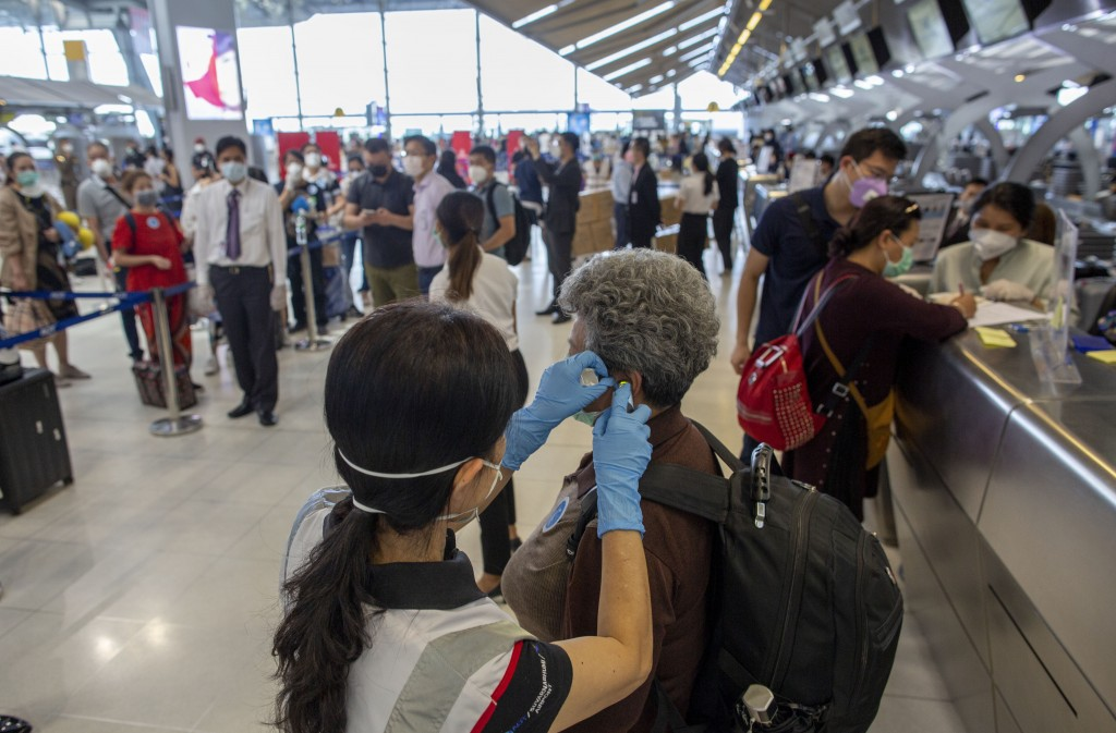 A health worker checks the temperature of a tourist from Wuhan, China, as she waits for a charter flight back to Wuhan at the Suvarnabhumi airport, Ba...