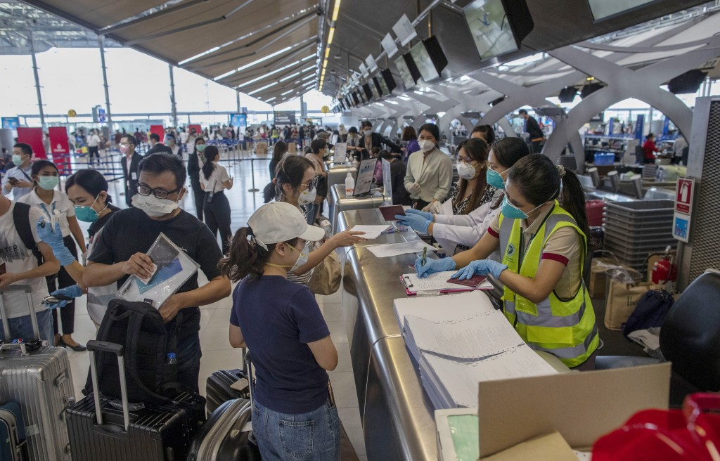 Tourists from Wuhan, China, go through health checks as wait for a charter flight back to Wuhan at the Suvarnabhumi airport, Bangkok, Thailand, Friday...