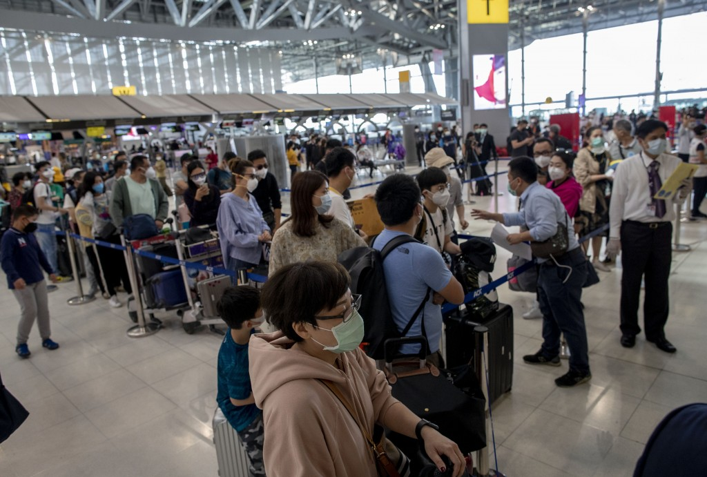 Tourists from Wuhan, China, stand in a line for a charter flight back to Wuhan at the Suvarnabhumi airport, Bangkok, Thailand, Friday, Jan. 31, 2020. ...