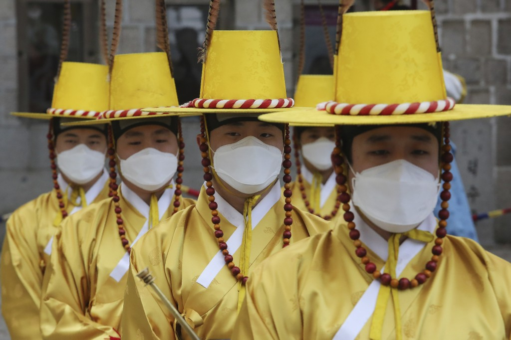In this Thursday, Jan. 30, 2020, file photo, imperial guards wear protective face masks during a reenactment of the Royal Guards Changing Ceremony in ...