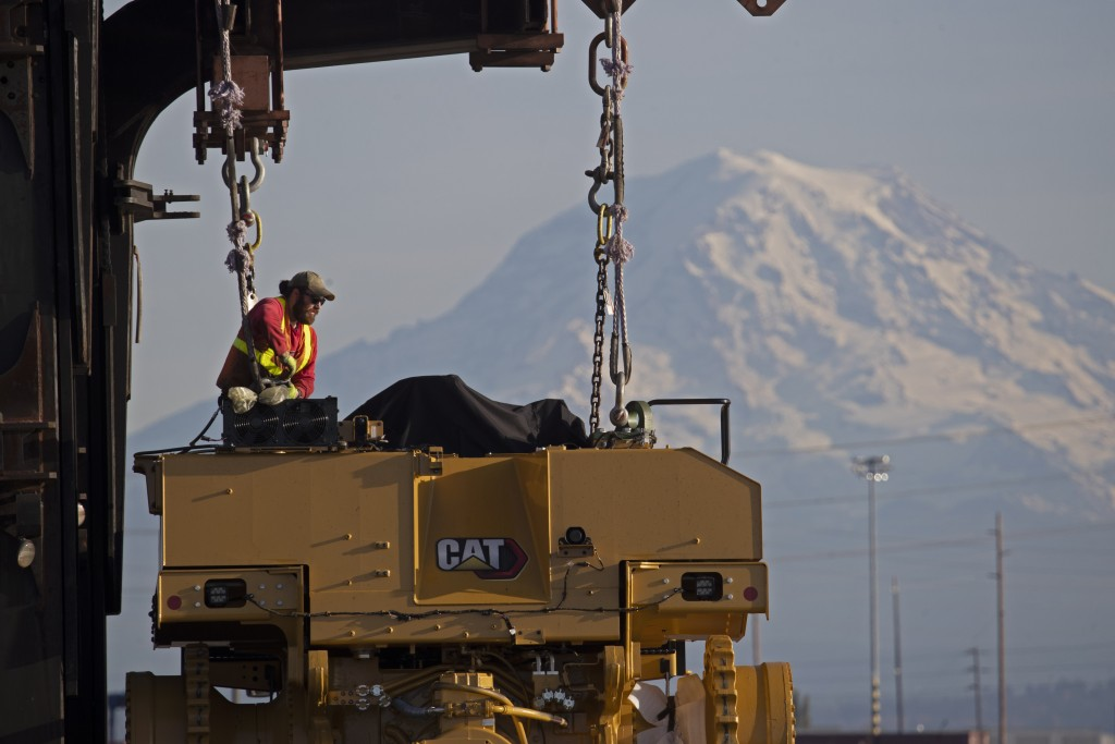 FILE - In this Nov. 4, 2019, file photo a worker prepares a piece of Cat construction equipment made by Caterpillar to be lifted off a trailer at the ...