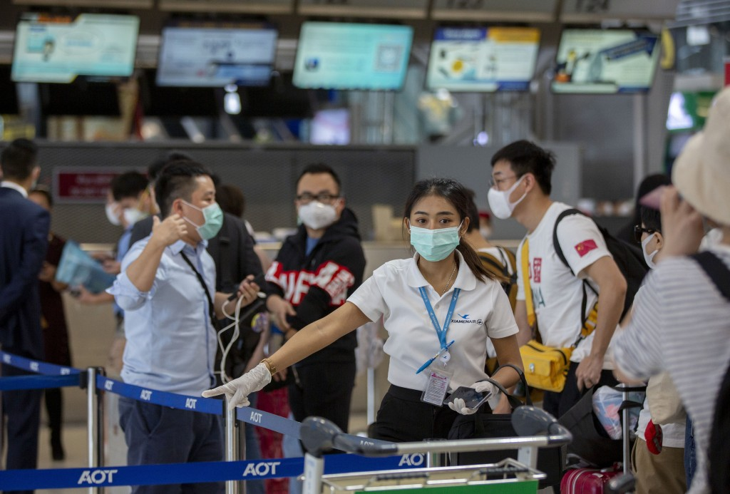 An airline staffer assists tourists from Wuhan, china, as they wait for a charter flight back to Wuhan at the Suvarnabhumi airport, Bangkok, Thailand,...