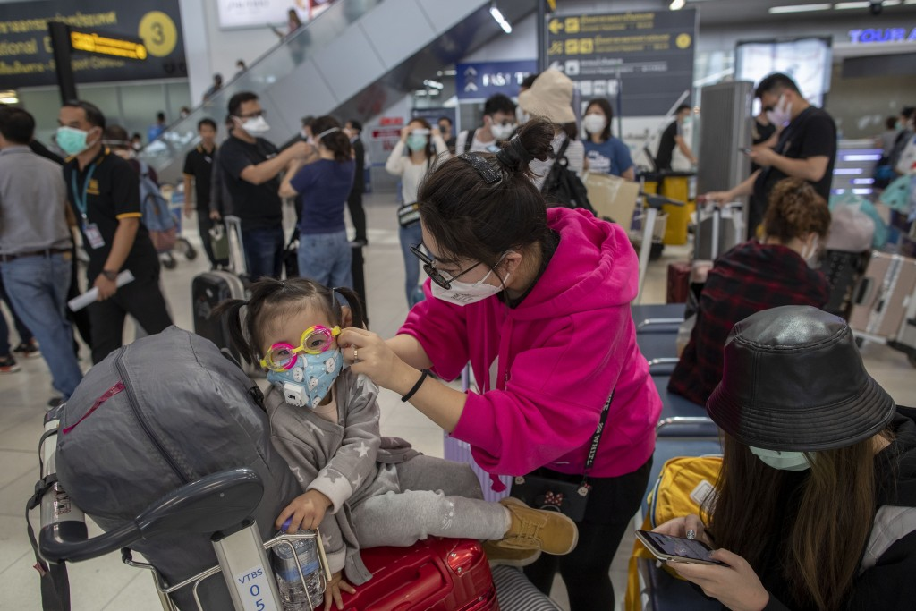 A tourist from Wuhan, China, adjusts the face mask of a child as they stand in a line for a charter flight back to Wuhan at the Suvarnabhumi airport, ...