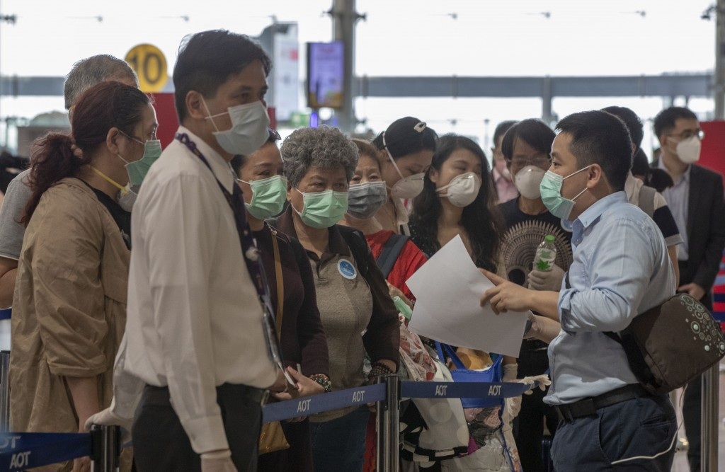 Airport officials speak with tourists from Wuhan, China, a they prepare to take a charter flight back to Wuhan at the Suvarnabhumi airport, Bangkok, T...