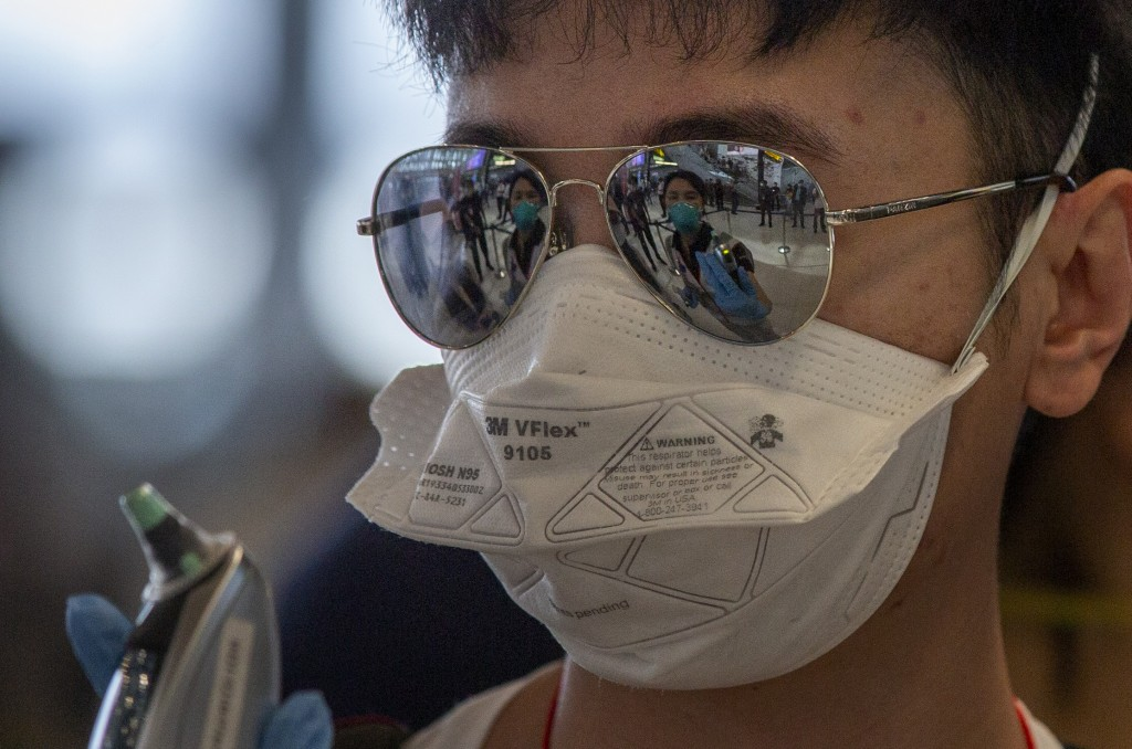 A health worker with a thermometer is mirrored in a sun glasses of a tourist from Wuhan, China as he stands in a line for a charter flight back to Wuh...
