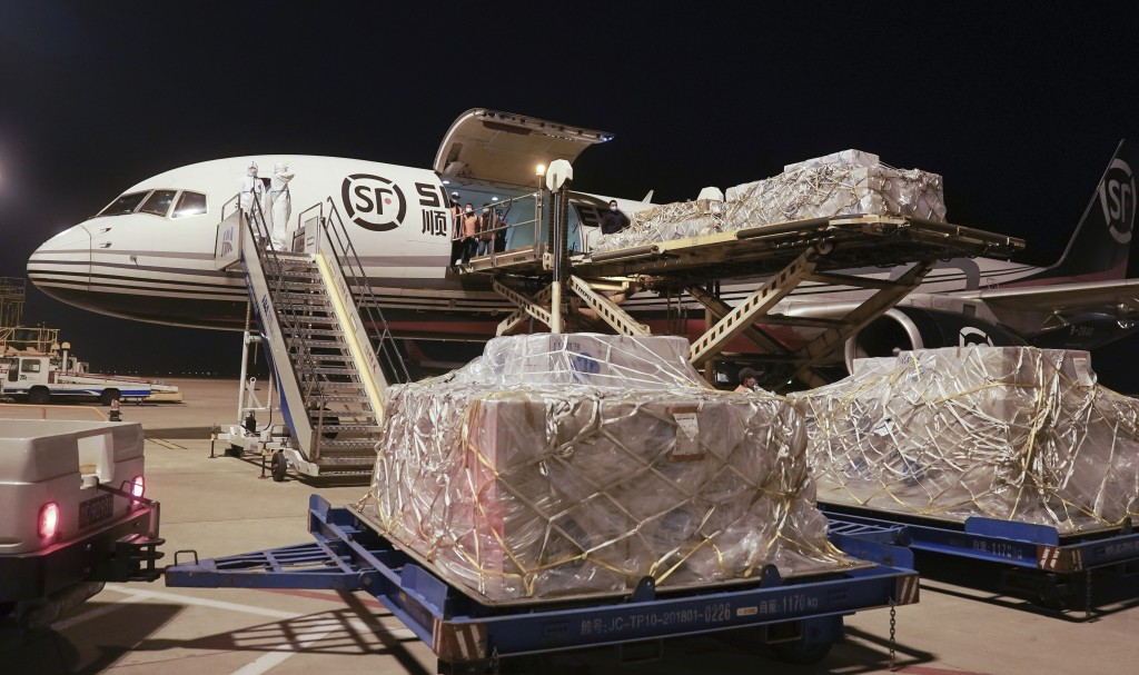 In this Jan. 30, 2020 photo released by China's Xinhua News Agency, workers unload a shipment of protective suits from a cargo plane at Wuhan Tianhe I...