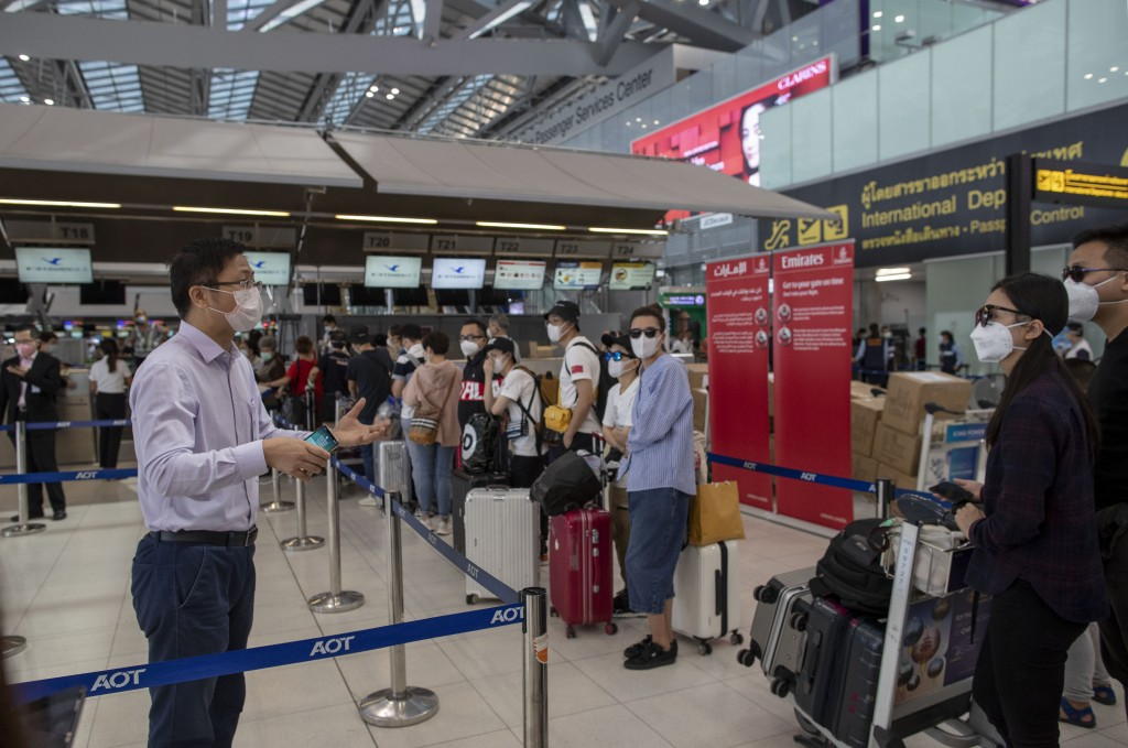 An airport official speaks with tourists from Wuhan, China, waiting for a charter flight back to Wuhan at the Suvarnabhumi airport, Bangkok, Thailand,...
