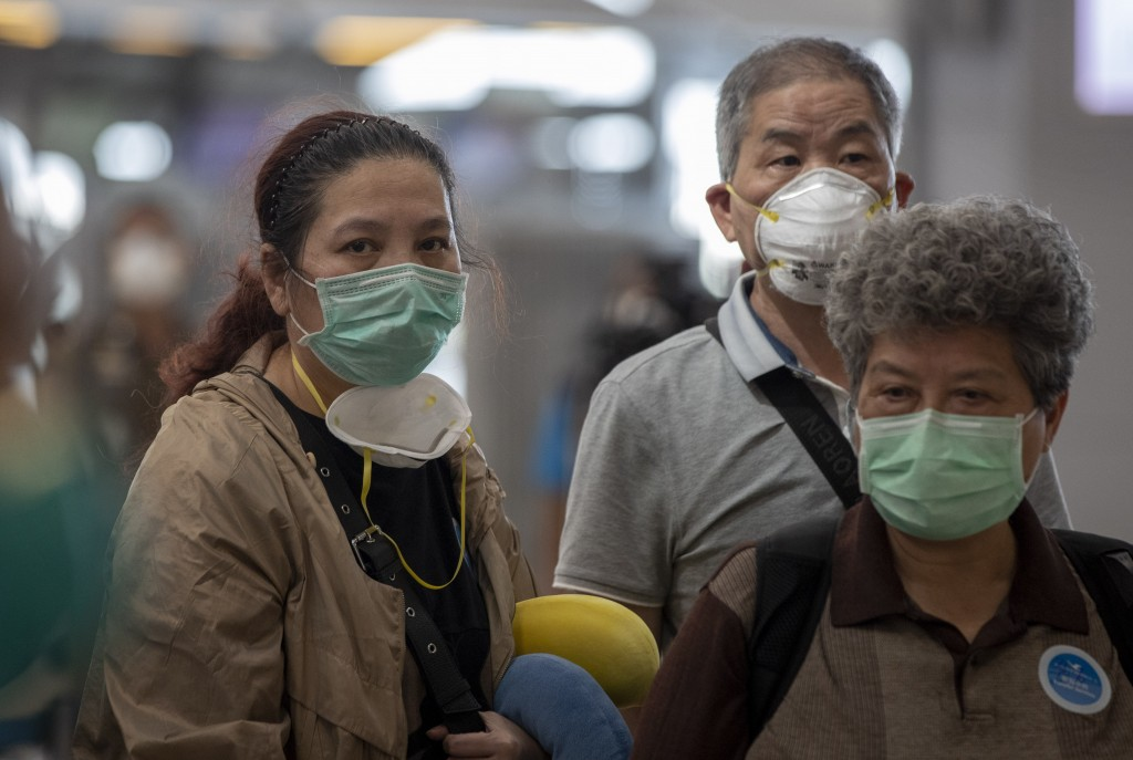 Tourists from Wuhan, China, some with double face masks, stand in a line for a charter flight back to Wuhan at the Suvarnabhumi airport, Bangkok, Thai...