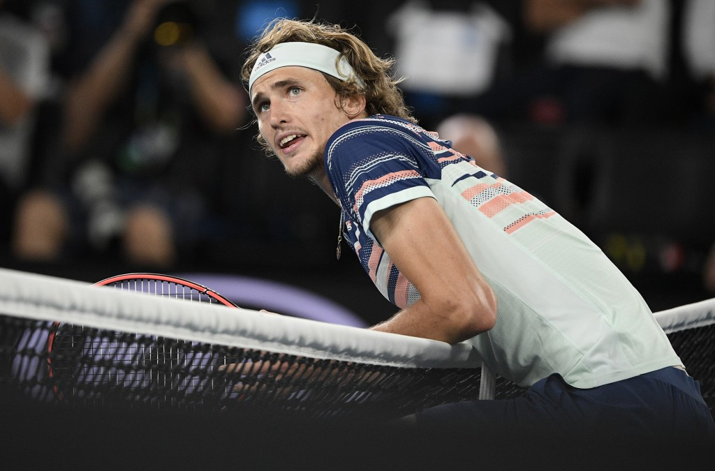 Germany's Alexander Zverev rests on the net as he argues with the chair umpire over a line call during his semifinal match against Austria's Dominic T...